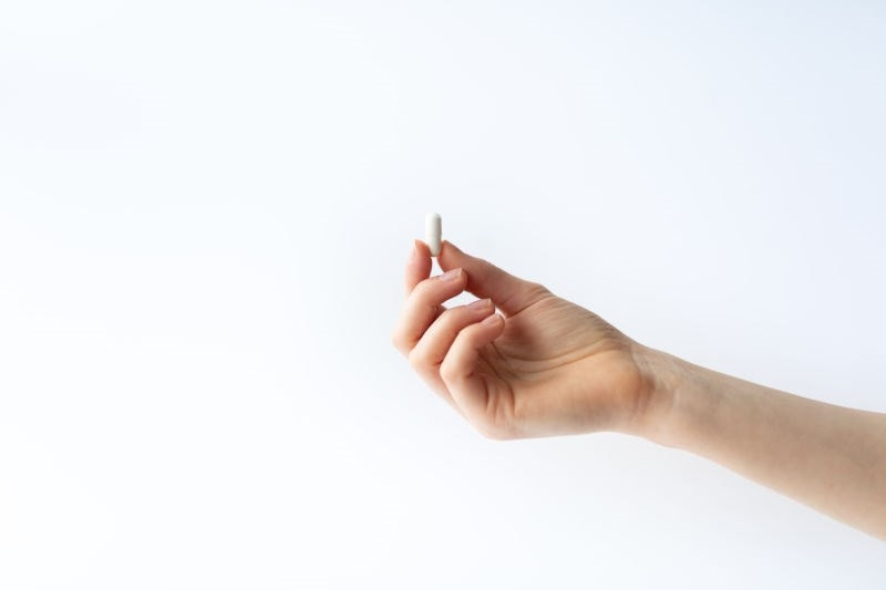 hand holding up a supplement capsule