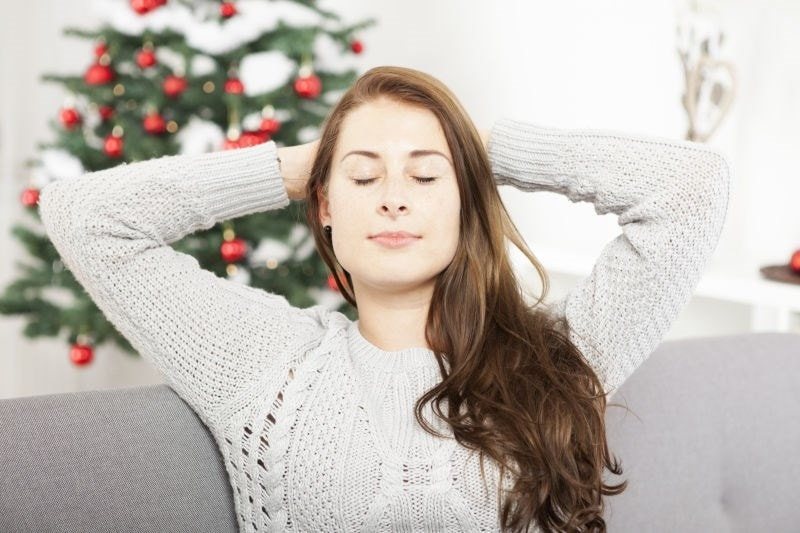 woman relaxed beside christmas tree