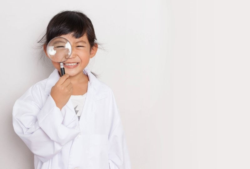 child holding magnifying glass