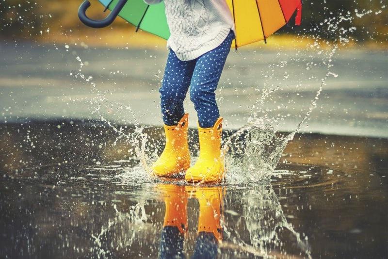 child splashing in puddles