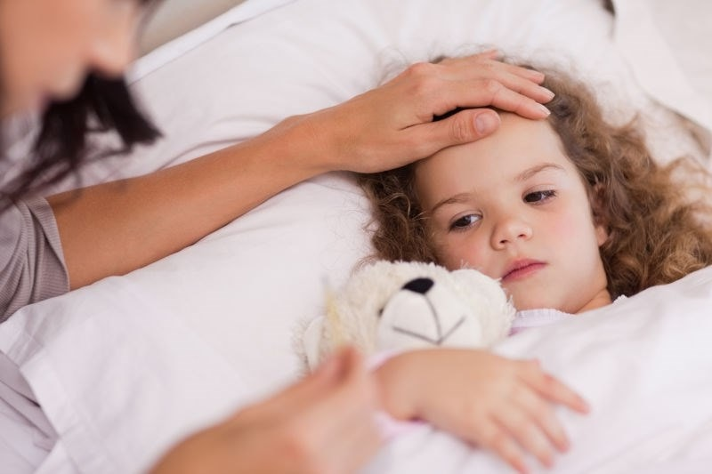 Child unwell lying in bed