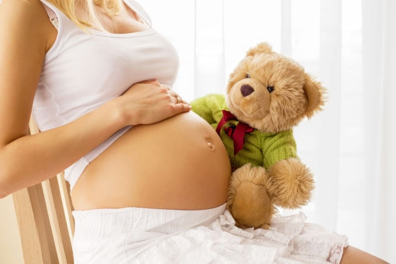 Pregnant woman sitting with teddy