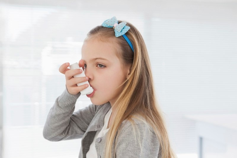 girl taking inhaler