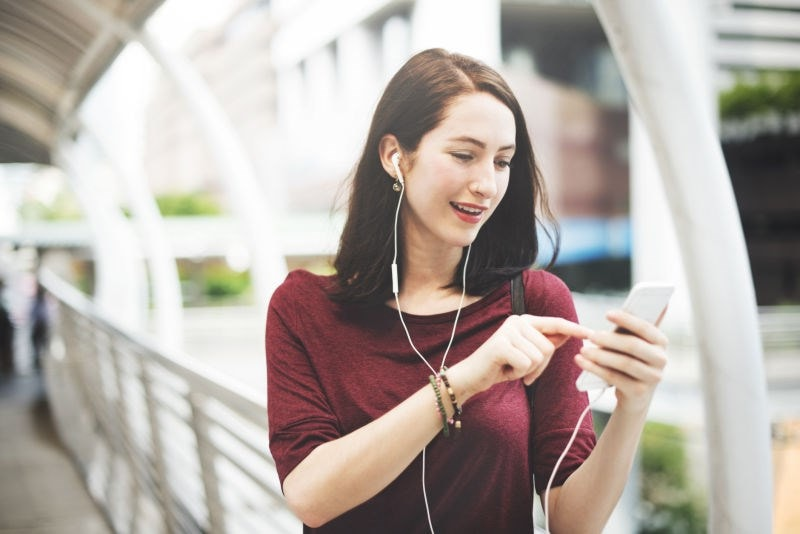 female listening to earphones from phone