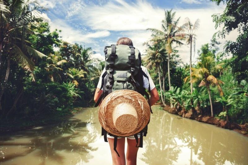 backpacker walking through rainforest water