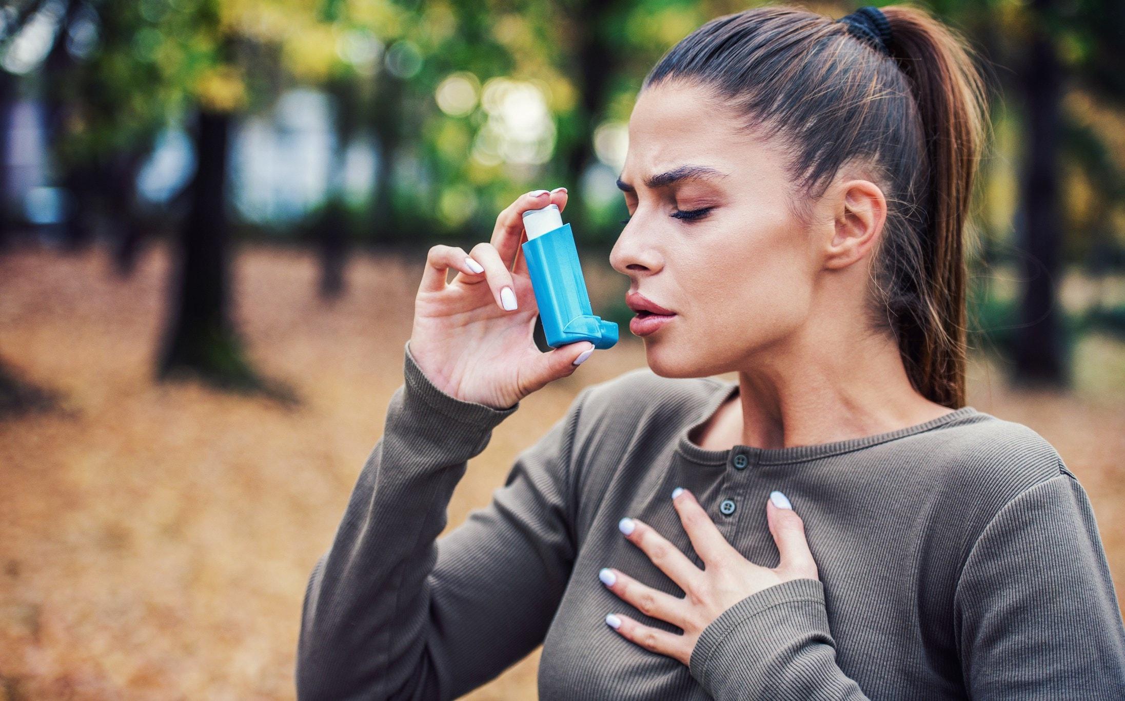woman taking her inhaler