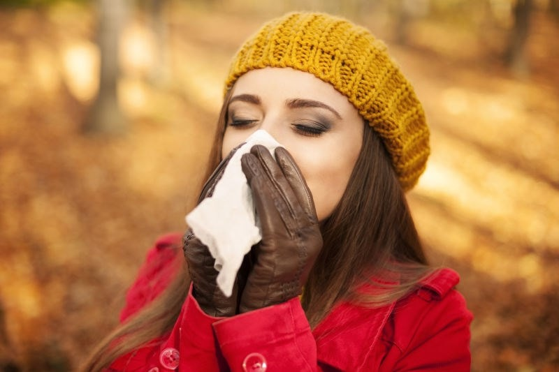 woman holding tissue to face