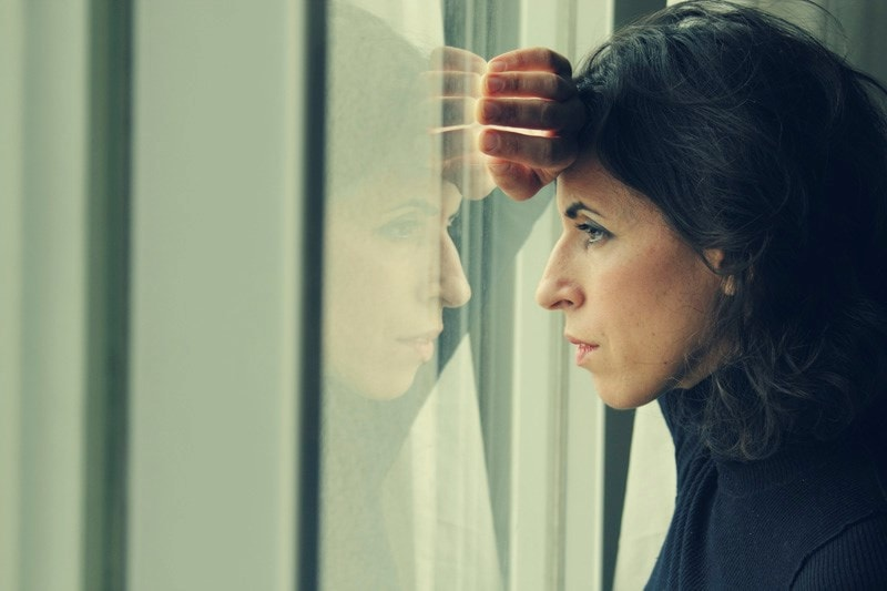 woman looking anxiously out the window