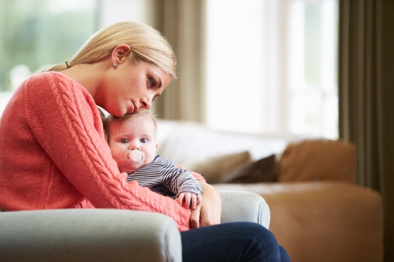 Stressed and upset mother holding newborn