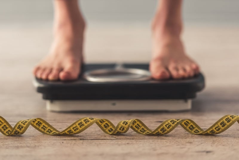 Feet on scales with measuring tape