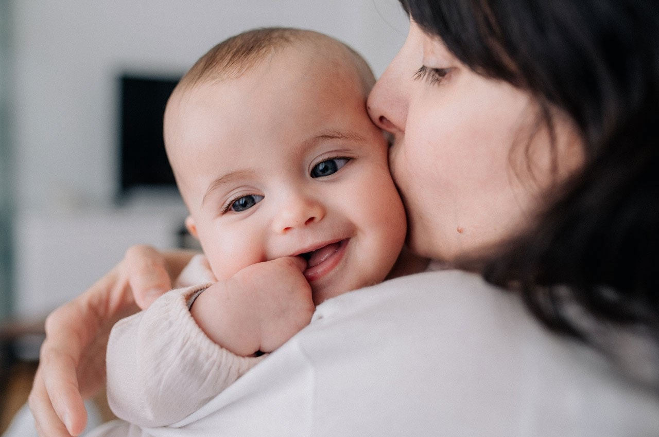 Mother kissing smiling baby
