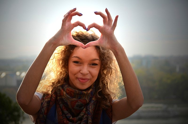 Woman holding up hands in heart shape