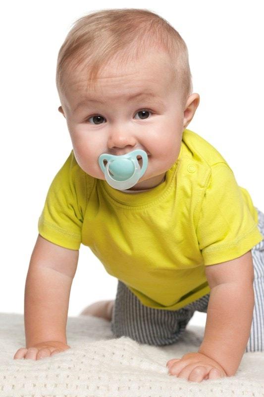 Crawling baby sucking a dummy