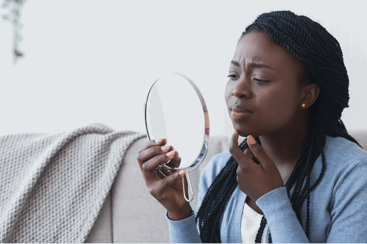 woman looking in mirror at her face